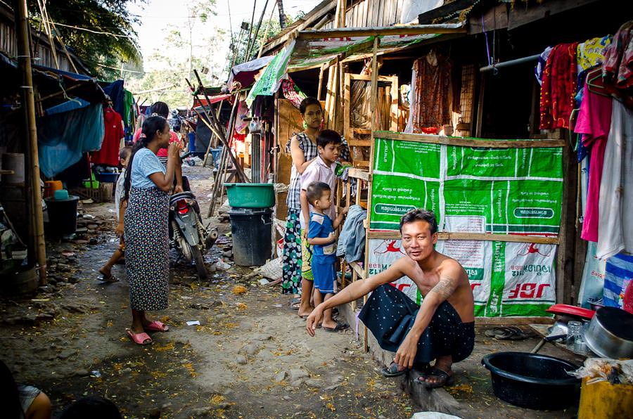 A man sits outside his simple home in Myawaddy, Myanmar.