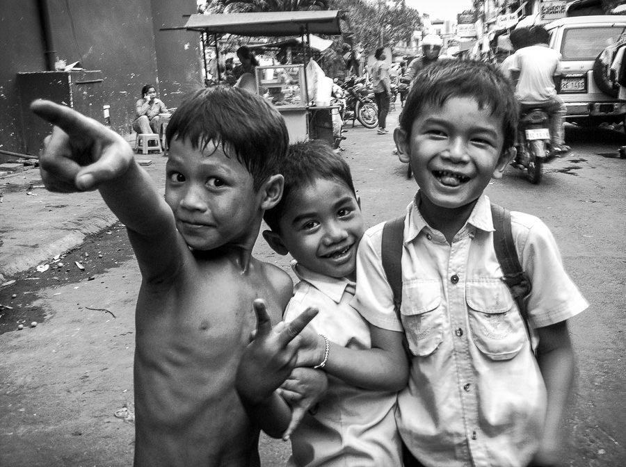 Three young boys play on the street outside the white building in Phnom Penh, Cambodia.