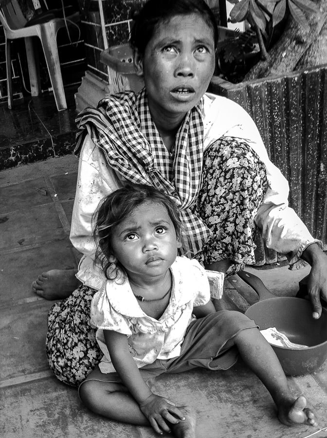 A mother and her daughter begging for money outside a restaurant in Kampong Cham, Cambodia.