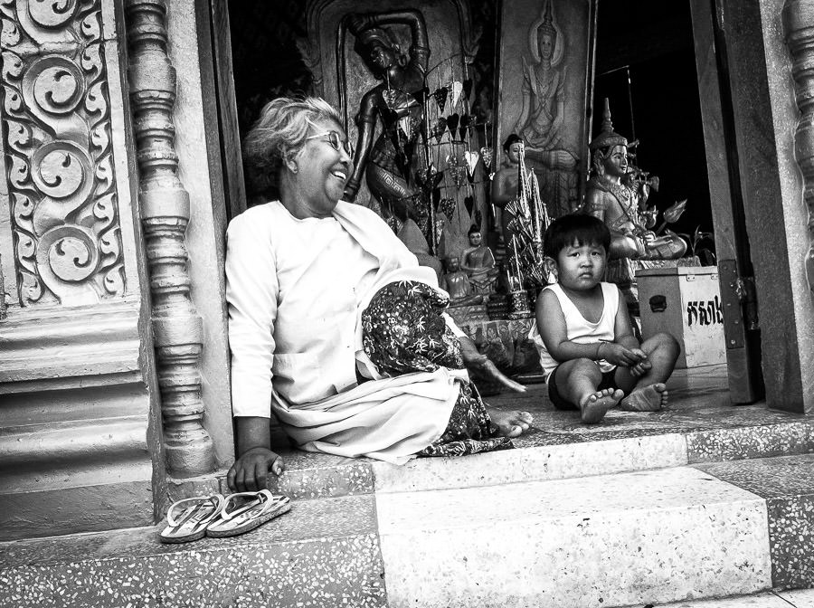 An old woman and a young boy sit in the entrance of the temple in Battambang, Cambodia.