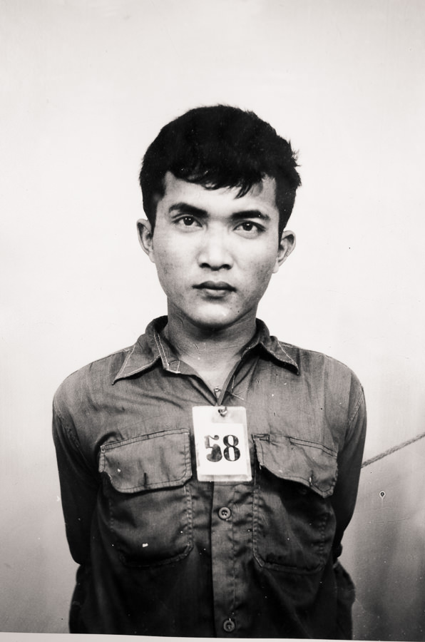 Black and white photo of a prisoner at S-21, Tuol Sleng in Phnom Penh