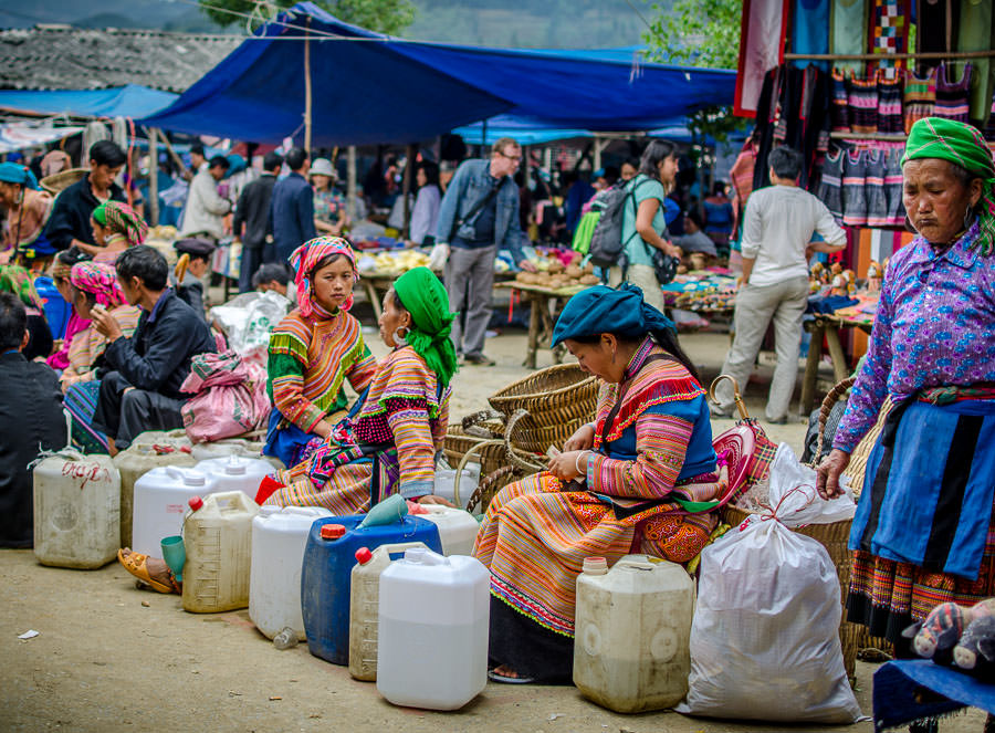 Hilltribe women at the market in Bac Ha selling rice wine, happy water.