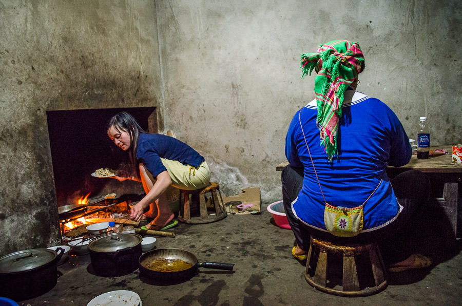A mother and daughter cooking dinner at a homestay in Ta Van Village, Vietnam. Travel dangers in Vietnam.