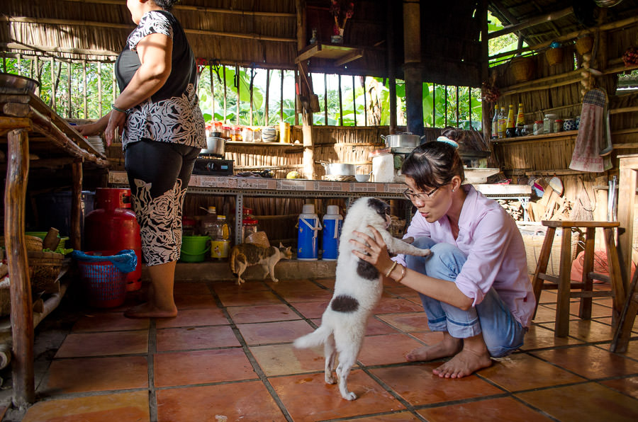 Our guide, Angie, playing with one of the puppies in the kitchen of the home stay.