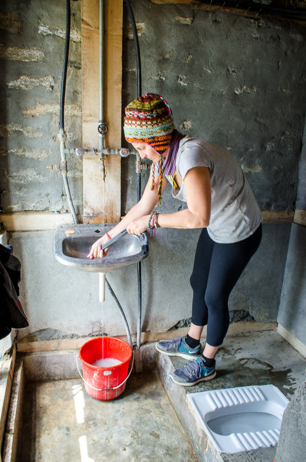Ashlie doing laundry in the bathroom in Manang village, Nepal